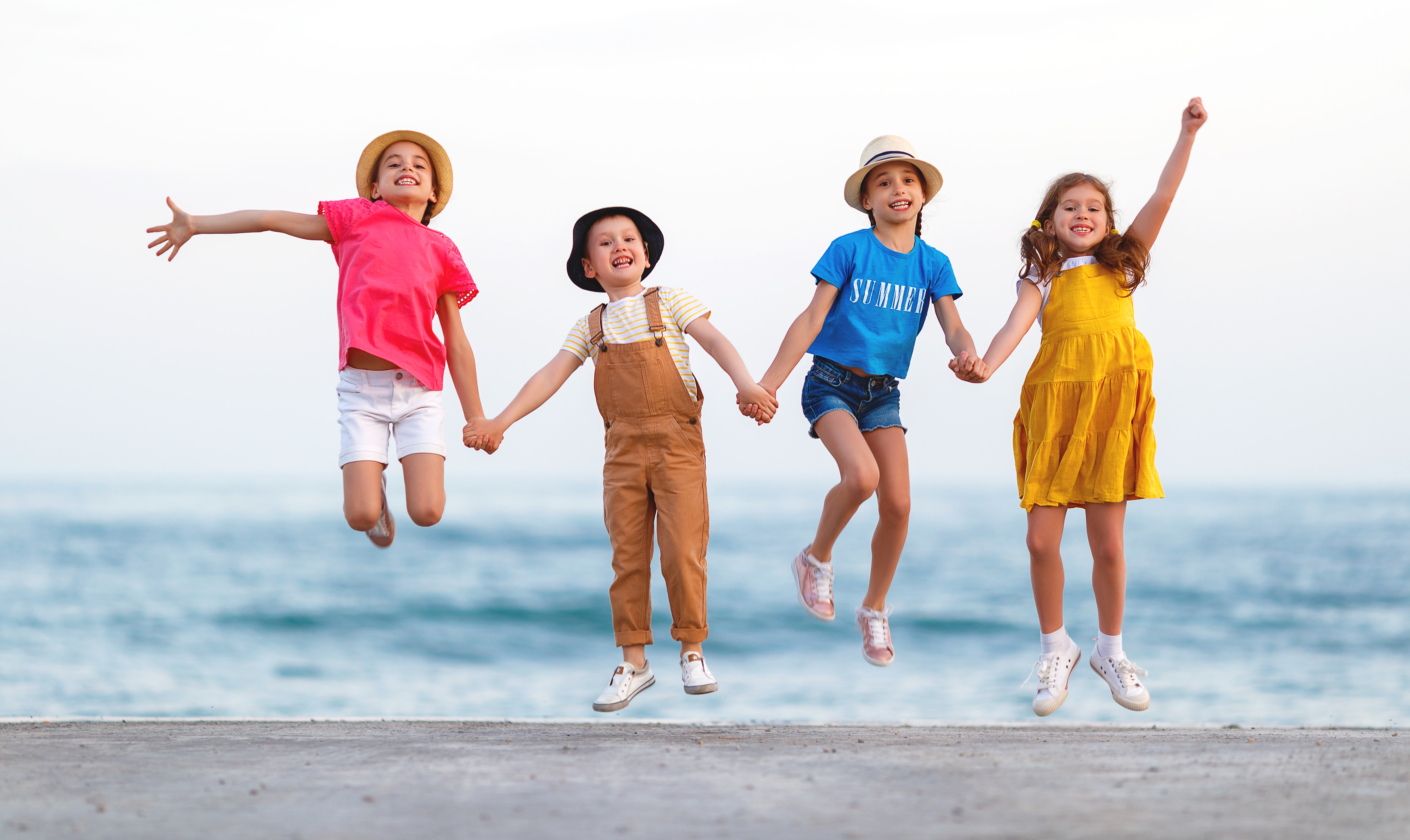 group of happy children jump by   sea in summer